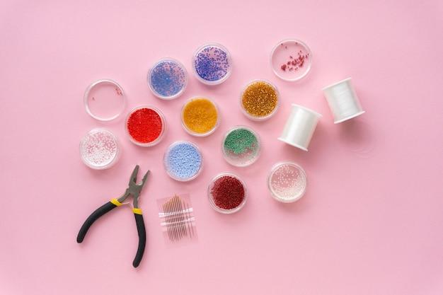 Camada plana de itens para criatividade. grânulos, linha de pesca e cortadores de fio em fundo rosa, copyspace.