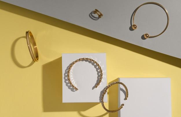 Camada plana de joias douradas em fundo amarelo e cinza