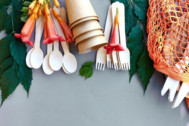 Camada plana de papel artesanal ecológico e talheres de madeira, desperdício zero, vida sem plástico e ecológica, copos de papel, pratos, saco, pratos e talheres de madeira em saco de malha de algodão.