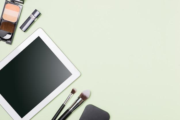 Camada plana de produtos cosméticos de maquiagem com tablet digital em fundo de cor clara