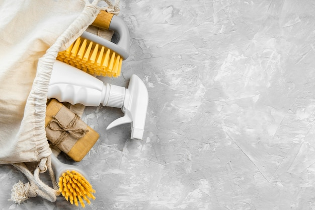 Camada plana de produtos de limpeza ecológicos com escovas e espaço de cópia