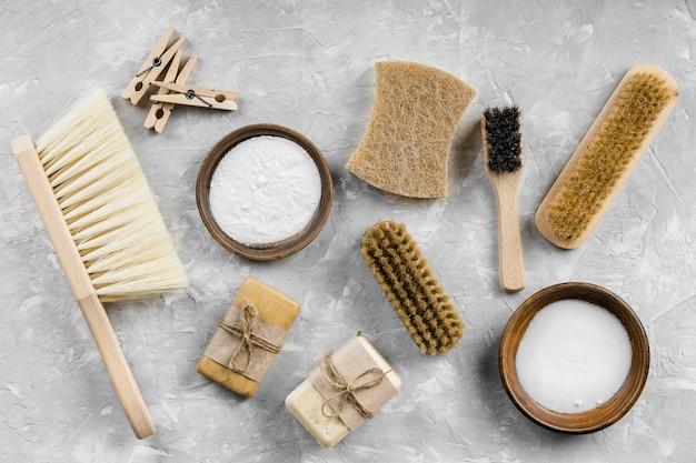 Camada plana de produtos de limpeza ecológicos com escovas e sabonetes