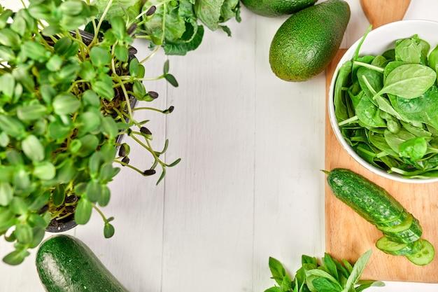 Camada plana de série de vegetais verdes variados e placa de madeira