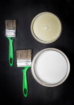 Camada plana, dois pincéis verdes e pratos com tinta, sobre um fundo preto texturizado com uma vinheta, vista superior.