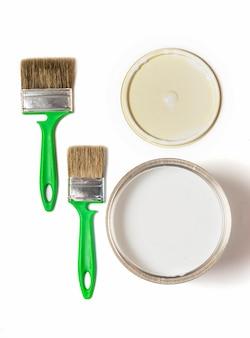 Camada plana, dois pincéis verdes e uma lata de tinta de ferro, sobre um fundo branco, vista de cima.
