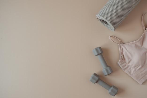 Camada plana e estética criativa de ioga, condicionamento físico e equipamentos de treino em bege neutro