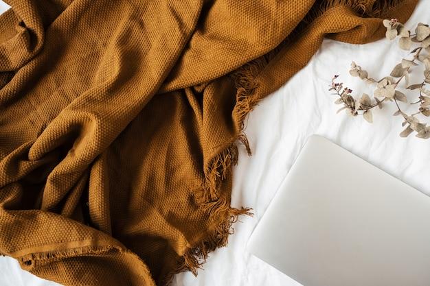 Camada plana mínima, composição de estilo de vida de vista superior com laptop, galho de eucalipto, manta de gengibre em linho branco