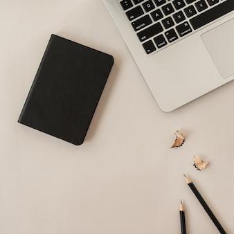 Camada plana mínima, composição de estilo de vida de vista superior com laptop, lápis, caderno em bege pastel neutro.
