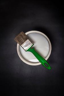 Camada plana, pincel verde e lata de ferro com tinta em plano de fundo texturizado preto.
