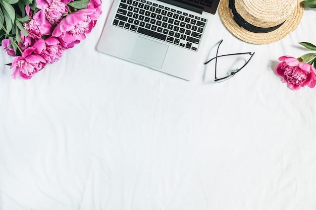 Camada plana, vista superior, área de trabalho com mesa de escritório feminino com laptop, buquê de flores de peônia rosa, óculos, chapéu de palha na superfície branca