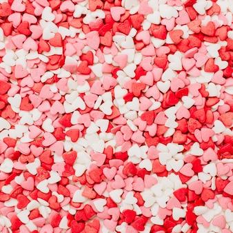 Camada plana, vista superior do padrão de corações vermelhos, rosa e brancos. conceito de amor.