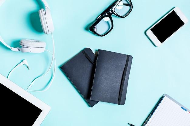 Camada plana, vista superior, simulação de local de trabalho com tablet, smartphone, notebook, caneta, fones de ouvido e óculos em um fundo turquesa