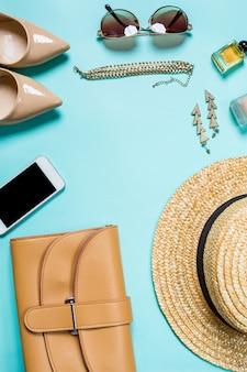 Camada plana, vista superior, simulação de roupas e acessórios femininos em um fundo turquesa. telefone, óculos de sol, pulseira, palha