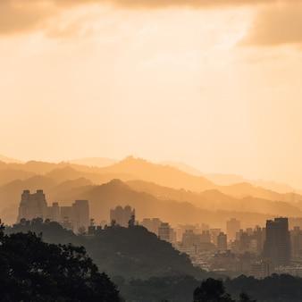 Camadas de arquitetura da cidade e de montanhas de taipei com luz solar quando o sol que vai abaixo dessa vista da montanha do elefante de xiangshan na noite em taipei, formosa.
