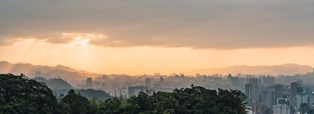 Camadas de arquitetura da cidade e de montanhas de taipei do panorama com luz solar quando o sol que vai para baixo.