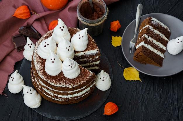Camadas de bolo de chocolate com creme de chocolate branco e fantasmas de merengue por cima. ideia de comida para festa de halloween.