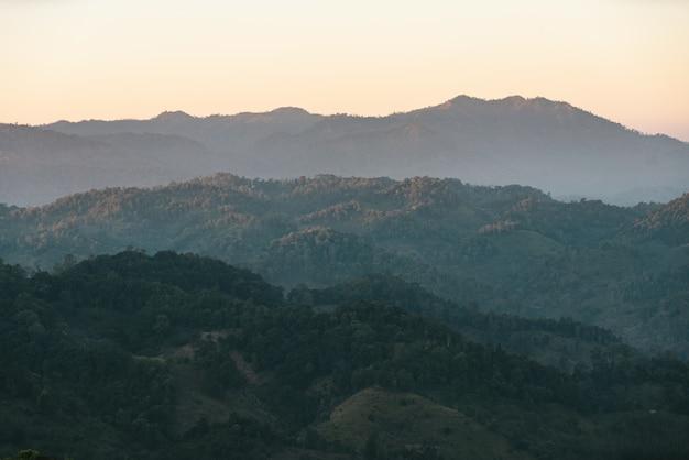 Camadas de montanha com luz solar e névoa na vila de akha de maejantai no monte em chiang mai, tailândia.