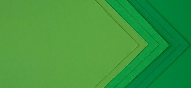 Camadas de papéis verdes criando setas abstratas