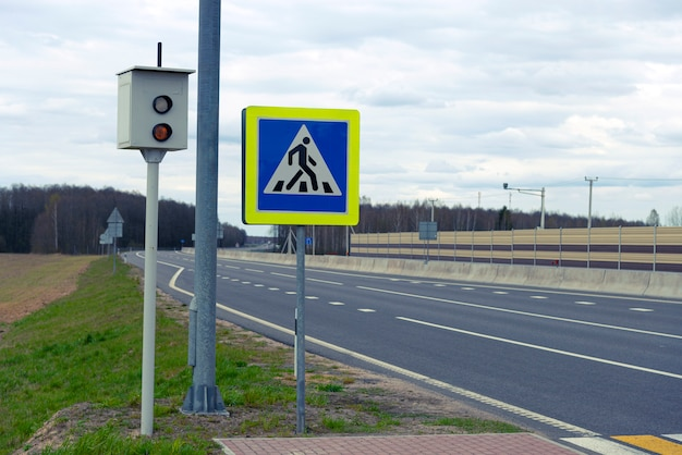 Câmara de velocidade numa estrada na europa e um sinal de trânsito de passagem para pedestres