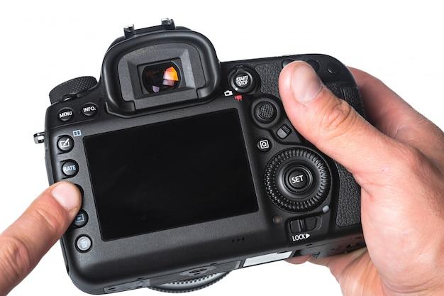 Câmara fotográfica na mão isolada no branco
