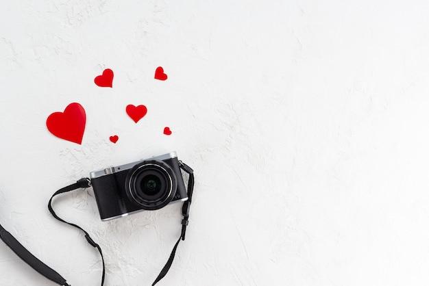 Câmara fotográfica retro com corações vermelhos sobre um fundo claro.