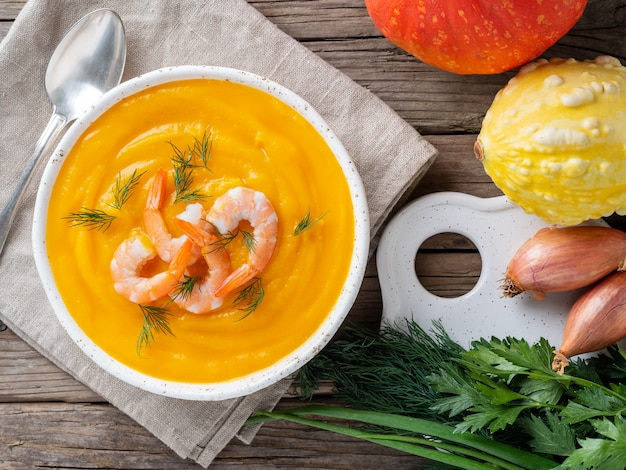 Camarão amarelo delicioso sopa creme de abóbora na mesa de madeira rústica velha cinza escura