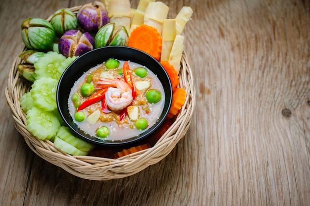 Camarão - cole o molho com legumes, omelete, cavala frita na mesa de madeira.
