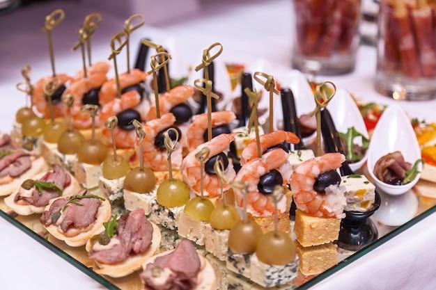 Camarão com azeitonas, queijo com uvas e canapés com carne. recepção de coquetel
