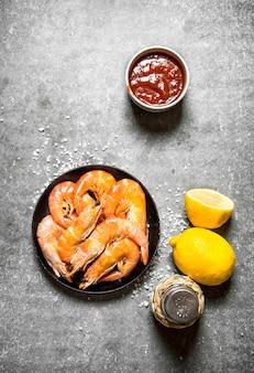 Camarão com molho de limão na mesa de pedra.