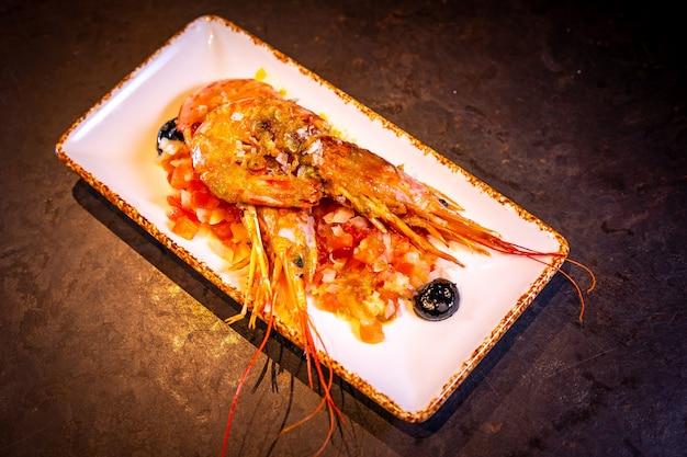 Camarão com molho em fundo preto, em prato branco