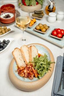 Camarão com rúcula e pão servido com vinho branco
