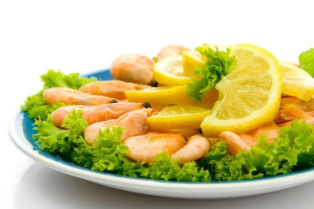 Camarão cozido com limão e folhas de alface no prato, isolado no branco