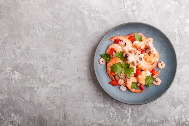 Camarão cozido ou camarão e polvos pequenos com ervas em uma placa de cerâmica azul sobre um fundo cinza de concreto