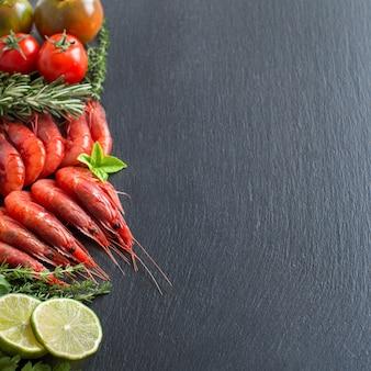 Camarão cru com tomate, limão e ervas em uma mesa escura com espaço de cópia