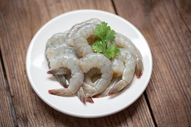 Camarão cru na chapa branca e fundo de madeira para cozinhar. close-up camarão fresco ou camarão frutos do mar egoísta