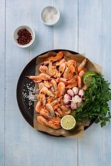 Camarão cru na panela com ingredientes para a preparação de camarão frito vista superior