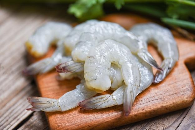 Camarão cru no fundo de madeira da placa de corte para cozinhar. close-up camarão fresco ou camarão frutos do mar egoísta