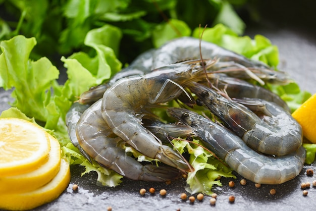 Camarão cru no prato, camarão fresco camarão cru com especiarias limão e salada de legumes alface ou carvalho verde sobre fundo escuro no restaurante de frutos do mar