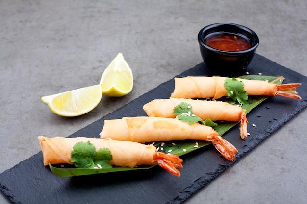 Camarão decorado com empréstimo e salsa, molho, em uma bandeja preta na moda, sobre um fundo cinza. o conceito de produtos marinhos.