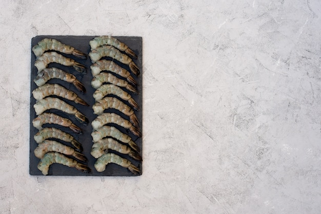Camarão descascado cru fresco em uma placa de pedra. frutos do mar saudáveis são uma fonte de proteína. postura plana. copie o espaço.