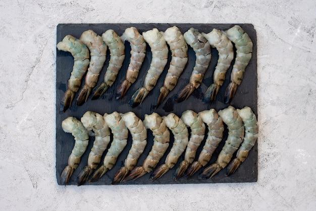 Camarão descascado cru fresco em uma placa de pedra. frutos do mar saudáveis são uma fonte de proteína. postura plana.