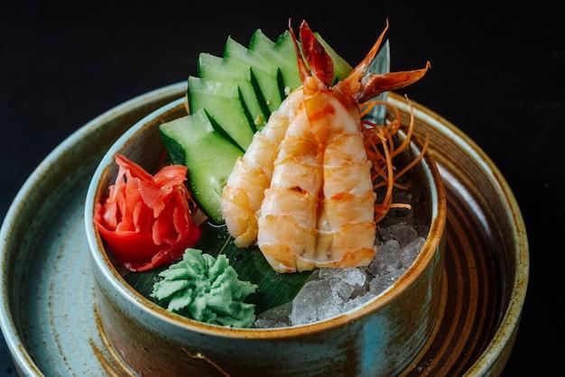 Camarão descascado vista frontal com wasabi de pepino picado e gengibre no gelo
