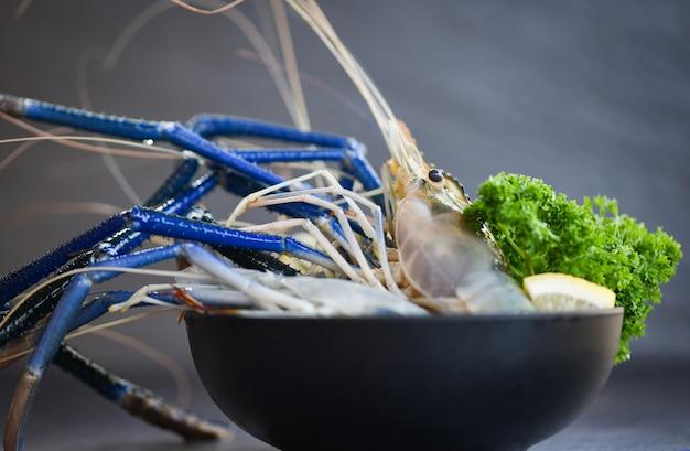 Camarão fresco de camarão com salsa de limão verde e especiarias para cozinhar comida tailandesa de tom yum kung em fundo escuro no restaurante de frutos do mar - camarão cru na tigela