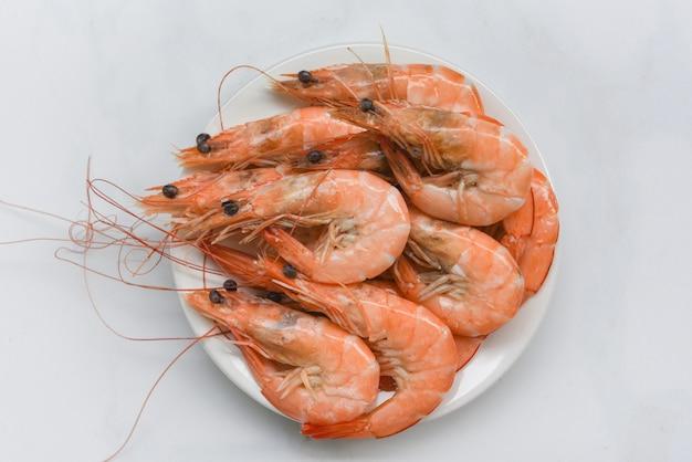 Camarão fresco em chapa branca - cozinhar camarão camarão frutos do mar servido em um fundo de mesa de comida
