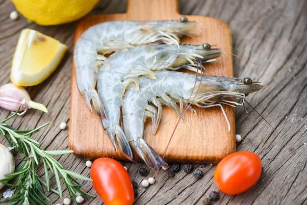 Camarão fresco na tábua de madeira com ingredientes ervas e especiarias para cozinhar frutos do mar - camarão cru camarão