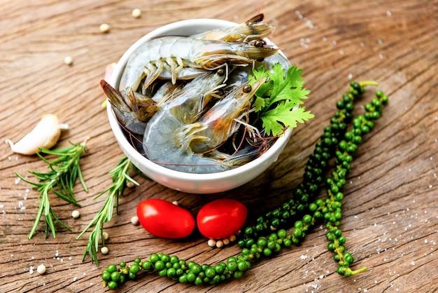 Camarão fresco na tigela branca e de madeira com ingredientes ervas e especiarias para cozinhar frutos do mar - camarão cru camarão
