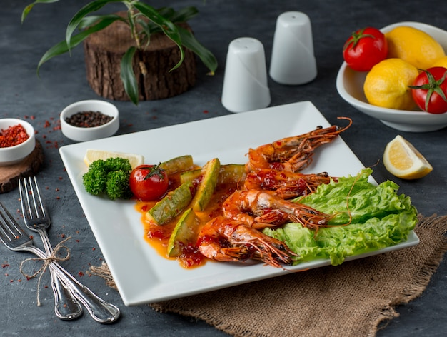Camarão frito com legumes em cima da mesa