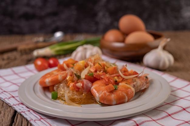 Camarão frito com macarrão de vidro em um prato branco colocado sobre um pano com ovos e alho.