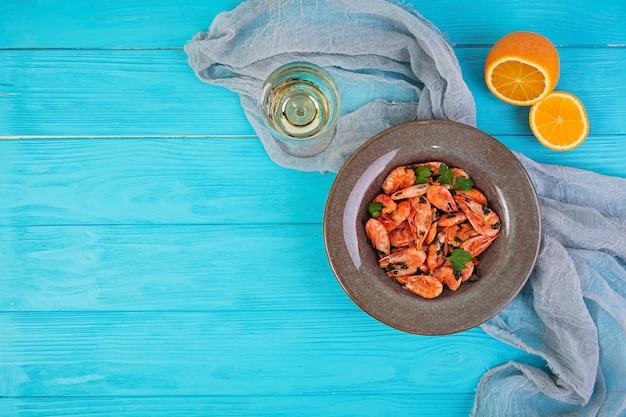 Camarão frito com molho de laranja picante em fundo de madeira