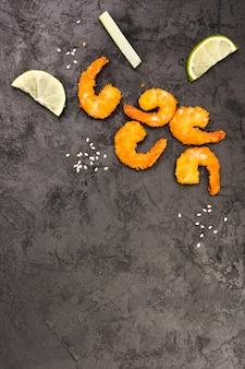 Camarão frito dourado com sementes de gergelim e fatias de limão sobre a superfície preta áspera